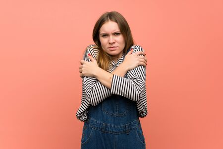 Young woman with overalls over pink wall freezing