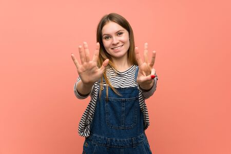 Young woman with overalls over pink wall counting eight with fingers Standard-Bild