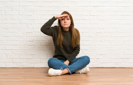 Young woman sitting on the floor looking far away with hand to look something