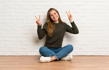 Young woman sitting on the floor showing victory sign with both hands