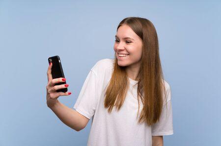 Junge Frau über blauer Wand macht ein Selfie