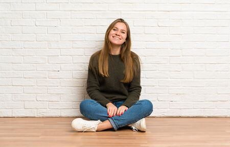 Young woman sitting on the floor smiling Stockfoto - 128616802