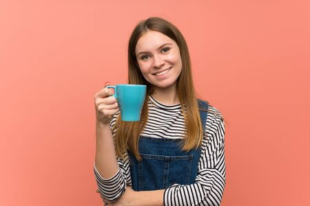 Young woman with overalls over pink wall holding a hot cup of coffee