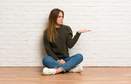 Young woman sitting on the floor holding copyspace with doubts Stockfoto - 128616974