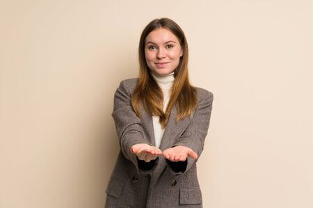 Young business woman holding copyspace imaginary on the palm to insert an ad Stock Photo