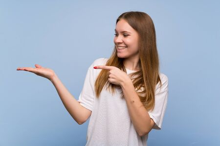 Young woman over blue wall holding copyspace imaginary on the palm to insert an ad Stock Photo