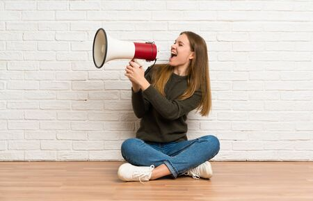 Young woman sitting on the floor shouting through a megaphone