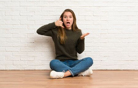 Young woman sitting on the floor making phone gesture and doubting