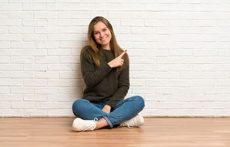Young woman sitting on the floor pointing to the side to present a product