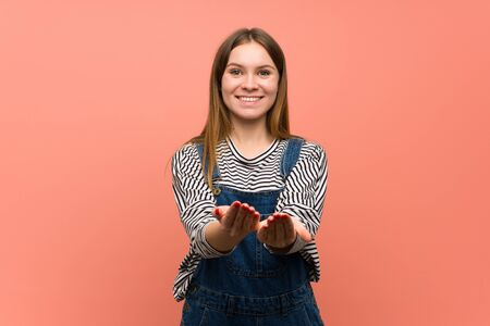 Young woman with overalls over pink wall holding copyspace imaginary on the palm to insert an ad