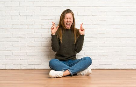 Young woman sitting on the floor with fingers crossing Stockfoto