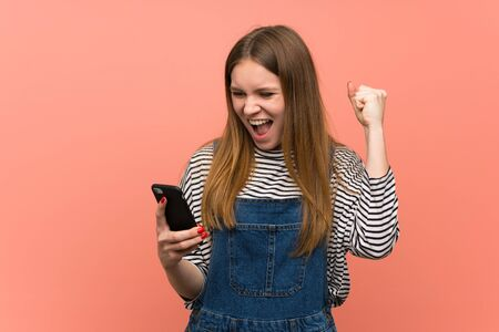 Young woman with overalls over pink wall celebrating a victory with a mobile Banque d'images - 128617441