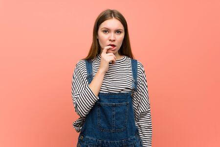 Young woman with overalls over pink wall having doubts while looking up Foto de archivo