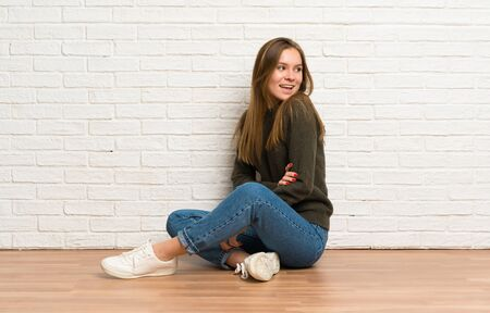 Young woman sitting on the floor with arms crossed and happy