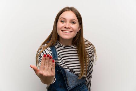 Giovane donna in salopette sul muro bianco che invita a venire