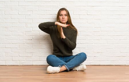 Young woman sitting on the floor making time out gesture Stockfoto