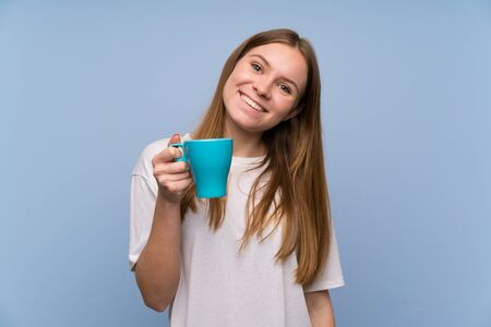 Young woman over blue wall holding a hot cup of coffee 写真素材