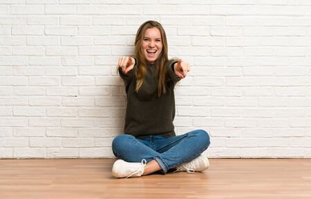 Young woman sitting on the floor points finger at you while smiling Stockfoto