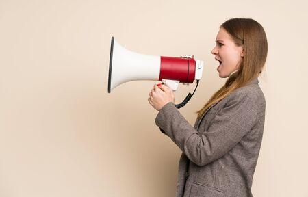 Junge Geschäftsfrau, die durch ein Megaphon schreit