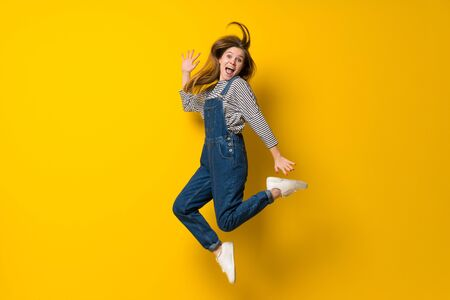 Young girl with overalls jumping over isolated yellow background