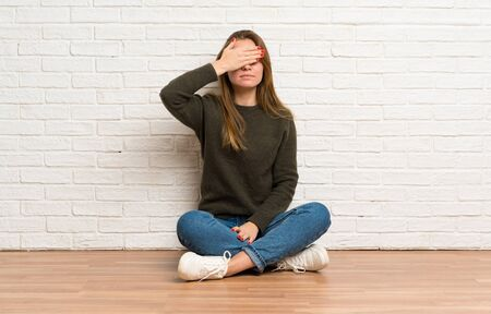 Young woman sitting on the floor covering eyes by hands. Do not want to see something Banco de Imagens