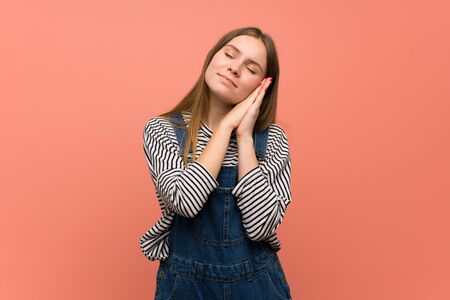 Young woman with overalls over pink wall making sleep gesture in dorable expression