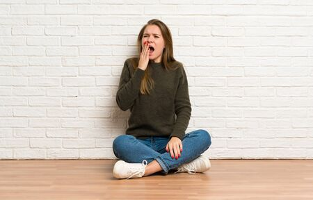 Young woman sitting on the floor yawning and covering wide open mouth with hand Banco de Imagens