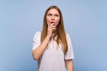 Mujer joven sobre pared azul teniendo dudas mientras mira hacia arriba