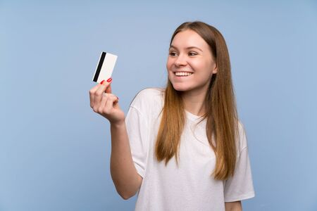 Young woman over blue wall holding a credit card and thinking Imagens