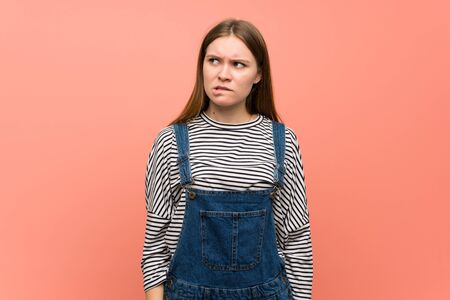 Young woman with overalls over pink wall with confuse face expression while bites lip