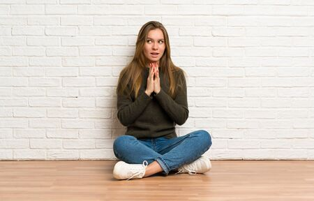 Young woman sitting on the floor scheming something