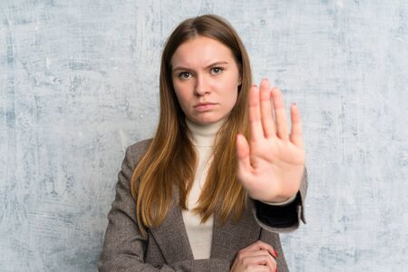 Young woman over grunge wall making stop gesture with her hand