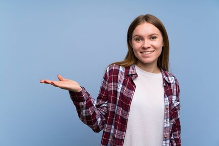 Young woman over blue wall holding copyspace imaginary on the palm