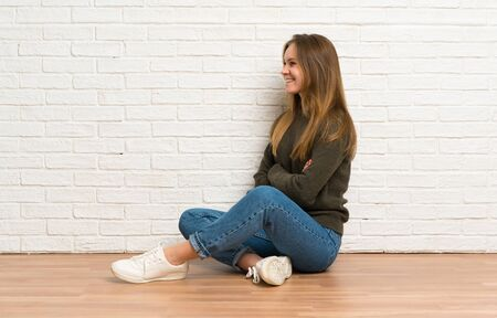 Young woman sitting on the floor in lateral position