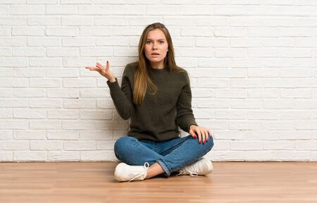 Young woman sitting on the floor making doubts gesture