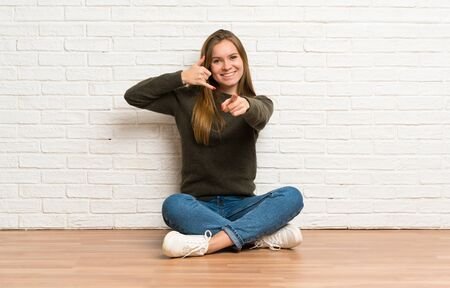 Young woman sitting on the floor making phone gesture and pointing front Stockfoto - 128617513
