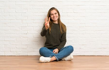 Young woman sitting on the floor happy and counting three with fingers