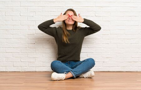 Young woman sitting on the floor covering eyes by hands