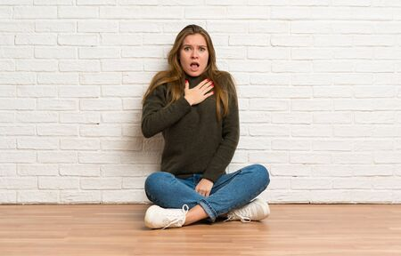 Young woman sitting on the floor surprised and shocked while looking right Stockfoto - 128617432