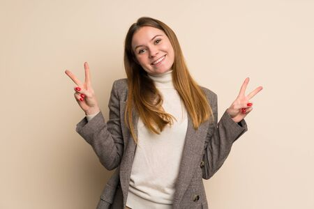 Young business woman showing victory sign with both hands Banque d'images - 128617434