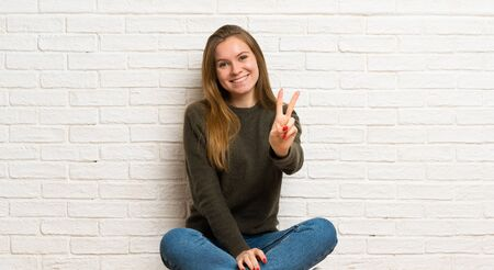 Young woman sitting on the floor smiling and showing victory sign Stockfoto - 128617387