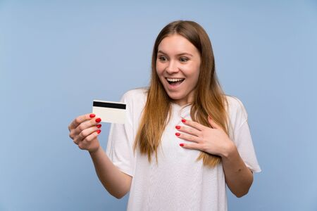 Young woman over blue wall holding a credit card and surprised Stock fotó