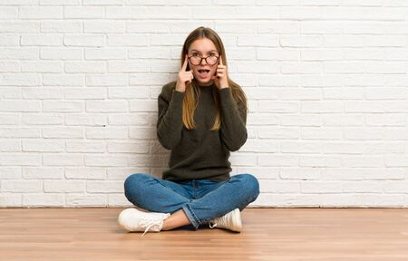 Young woman sitting on the floor with glasses and surprised Stockfoto - 128617398