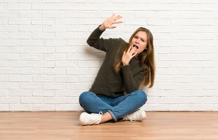 Young woman sitting on the floor nervous and scared Stockfoto - 128617395