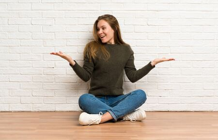 Young woman sitting on the floor holding copyspace with two hands
