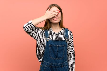 Young woman with overalls over pink wall covering eyes by hands. Do not want to see something