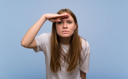 Young woman over blue wall looking far away with hand to look something 版權商用圖片