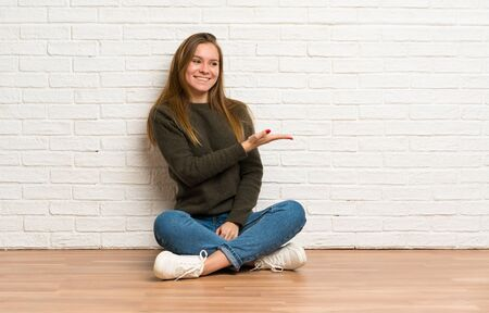 Young woman sitting on the floor presenting an idea while looking smiling towards Stockfoto - 128617131