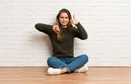 Young woman sitting on the floor making good-bad sign. Undecided between yes or not Stockfoto - 128617144