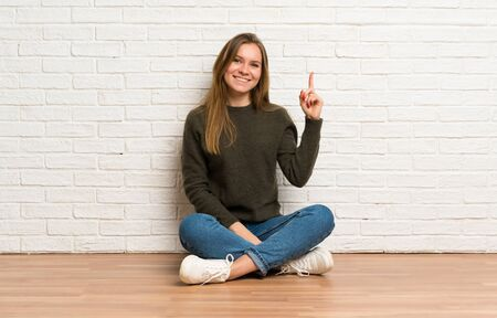 Young woman sitting on the floor showing and lifting a finger in sign of the best Stockfoto - 128617153